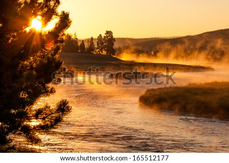 Sunrise above Yellowstone river. The vapor is still on the river. Early morning beams lights up part of the river. While other blue parts still need to warm up. - stock photo