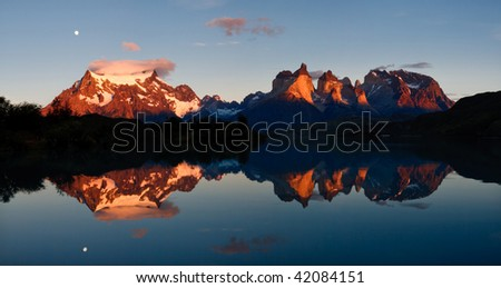 Sunrise & Alpenglow at Torres del Paine National Park, Patagonia, Chile: The Majestic Cuernos del Paine (Horns of Paine) Reflect in Lake (Lago) Pehoe. - stock photo