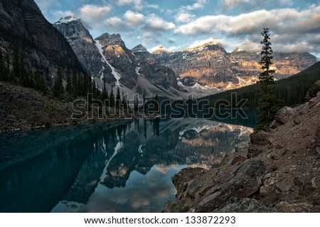 Sunrise and a beautiful reflection of the peaks around Moraine Lake. - stock photo