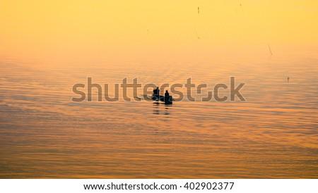 Sunrise and fisherman go to work at Bang Ta Boon bay,Phetchaburi province,Thailand,Soft focus - stock photo
