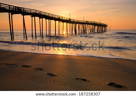 Sunrise and footprints on the Outer Banks, North Carolina - stock photo