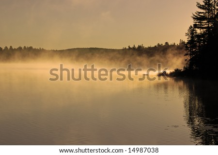 Sunrise and mist in beautiful lake in Algonquin Park - stock photo