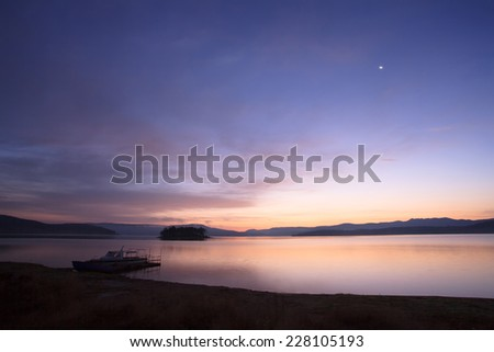 Sunrise and moon over the boat dock at high mountain lake  - stock photo