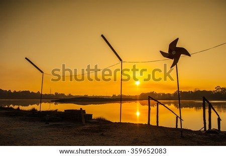 Sunrise and morning along the marsh small wind turbine energy innovation, clean energy, eco-friendly alternative  - stock photo