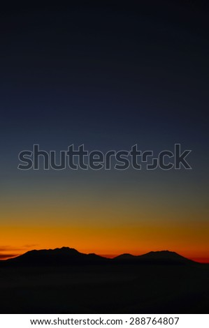 Sunrise and silhouette of Volcanoes in Bromo Tengger Semeru National Park - stock photo
