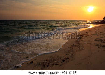 Sunrise and wave action on the beach - stock photo