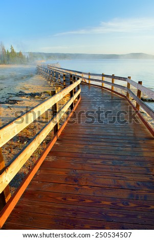 sunrise and wooden walkway in West Thumb area in Yellowstone National Park, Wyoming - stock photo