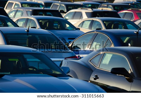Sunrise at a jam packed parking sales lot with many rows of automobiles. - stock photo