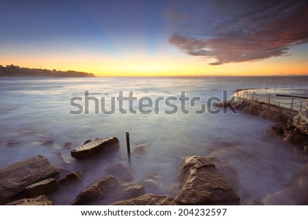 Sunrise at Bronte Beach south side near Bronte baths.  East Sydney.   One of the calmer moments as seas were high and turbulent.  Long Exposure. - stock photo