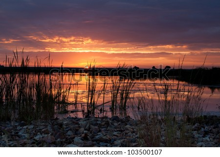 Sunrise at dam seen from the shore with beautiful colors - stock photo