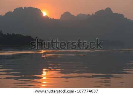 Sunrise at kayak on Rachapapha dam. Khao Sok National Park. Thailand. - stock photo