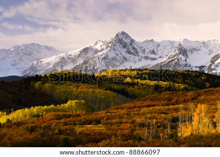 sunrise at mountain peaks in colorado with fall color - stock photo
