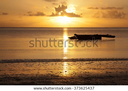 Sunrise at the beach with an African boat (dhow) at the foreground, Zanzibar, Tanzania - stock photo
