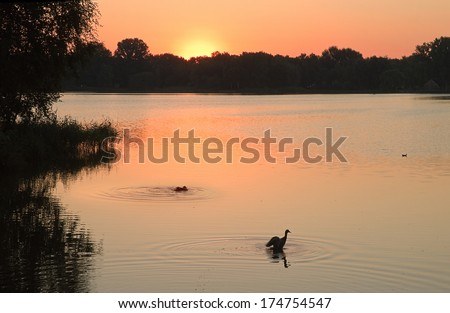 Sunrise at the lake with halo round the sun foretelling bad weather - stock photo