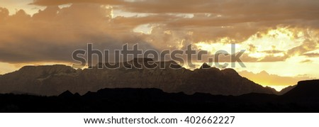 Sunrise behind West Temple mountain in Zion National park with silhouetted hills in the foreground  - stock photo