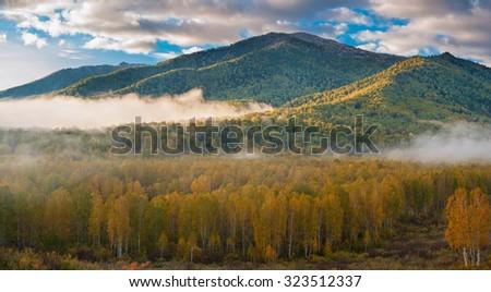 sunrise in autumn taiga and mountains - stock photo