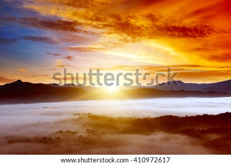 Sunrise in the mountains in the fog - stock photo