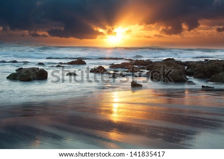 Sunrise landscape of ocean with waves clouds and rocks on beach - stock photo