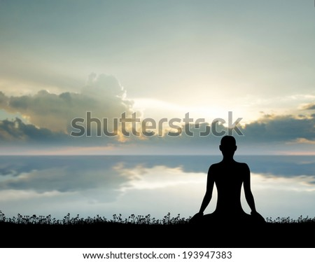 Sunrise meditation. Silhouette of a woman doing yoga exercise in the morning. - stock photo