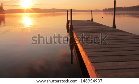 Sunrise on a dock in Maine - stock photo