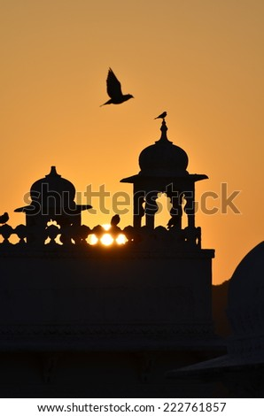Sunrise on a fort in India with silhouettes of birds  - stock photo