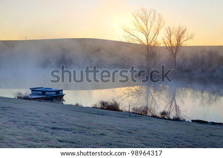 Sunrise on a misty morning over a lake - stock photo