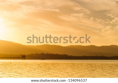 Sunrise on morning landscape, At the edge of the reservoir on mountain background - stock photo
