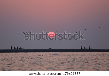 Sunrise on seashore with flying birds in Kuakata, Bangladesh - stock photo