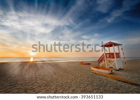 sunrise on the beach, lifeguard booth, sea, sun, summer, rest safe in the water - stock photo