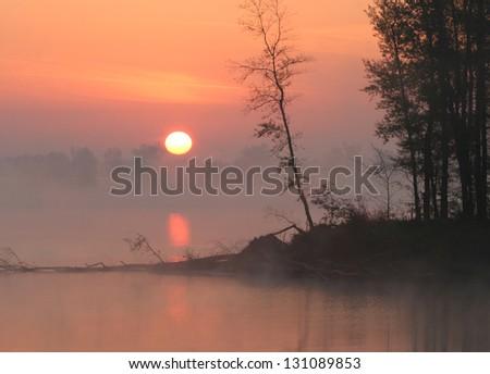 sunrise on the Kama River in the fog - stock photo