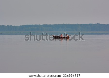 Sunrise on the lake - boat fishermen - stock photo