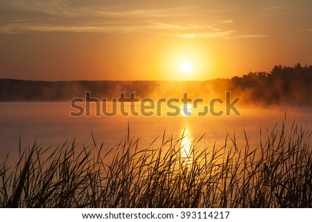 Sunrise on the lake. Early morning landscape. mist on the water, forest silhouettes and the rays of the rising sun. - stock photo