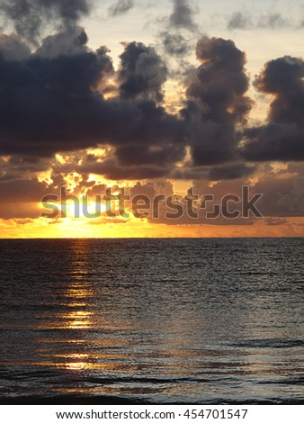 Sunrise on the ocean, during a cloudy day - stock photo