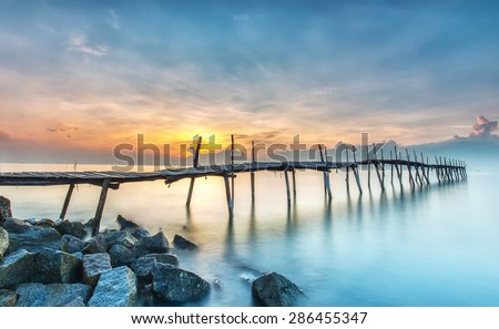 Sunrise on wooden bridge with dark yellow rays from the horizon beneath the long rustic wooden bridge in front of the sea basking beautiful smooth to start a new day - stock photo