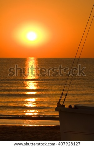 Sunrise or sunset at sea with silhouette of a small boat on the beach - stock photo