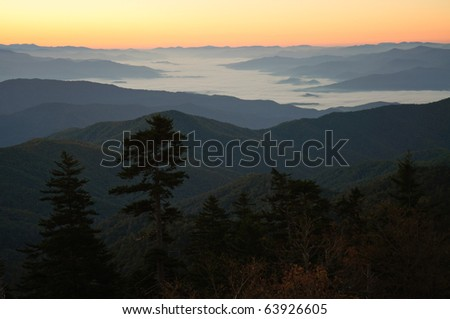sunrise over a foggy valley and mountain ranges - stock photo