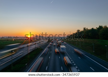 Sunrise over a highway near Brussels international airport, Belgium, Europe. Rush hour traffic concept with motion blur and text space. - stock photo