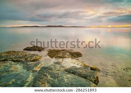 Sunrise over a very calm ocean with flat rocks in the foreground. - stock photo