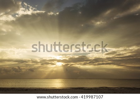 Sunrise over beach and ocea with beautiful colorful clouds and rays of lights - stock photo