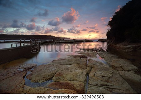 Sunrise over beautiful Malabar, just 12km from Sydney CBD.  This natural rock pool lies beside the man made one.  Malabar was named Boora by the local indigenous community. - stock photo