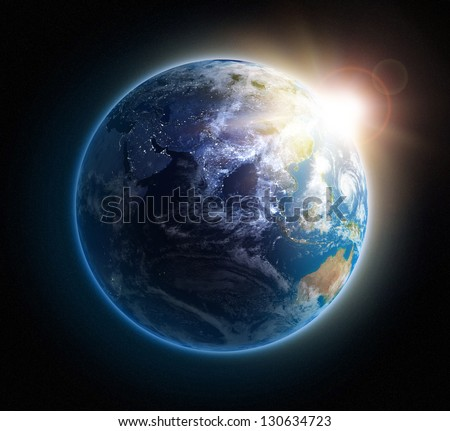 Sunrise over Earth seen from space with lights glowing in urban areas. - stock photo