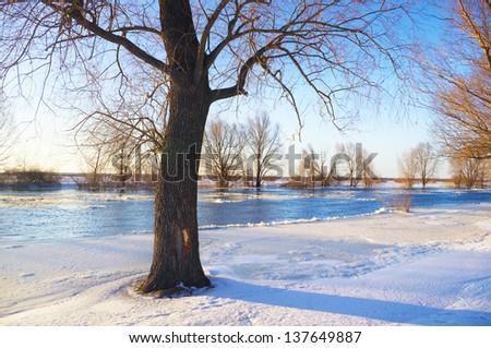 Sunrise over frozen river in winter - stock photo