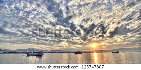 Sunrise over lake in south of thailand with finish boats in foreground and mountains in the distance - stock photo