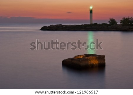 Sunrise over Lake Ontario with harbor and lighthouse - stock photo