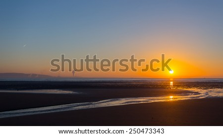 Sunrise over Swansea beach, South Wales, on a clear winter morning, with the industrial emissions from Port Talbot visible across the bay and a plane's contrail in the sky. - stock photo