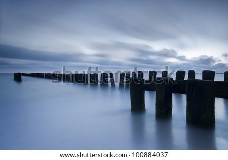 Sunrise over the Baltic sea, Poland. Photograph of breakwater minutes before sunrise. Long exposure photograph of sea and cloudy sky. Photograph has cold blue tone. - stock photo