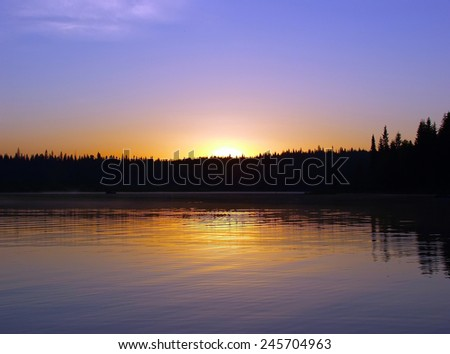 Sunrise over the lake and forest - stock photo