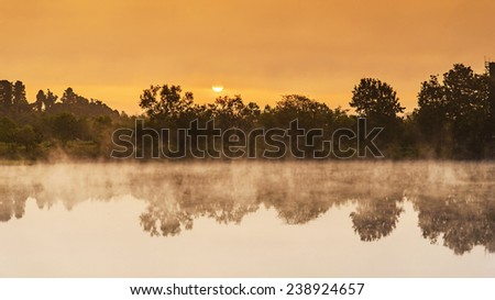Sunrise over the lake with the reflection of bare trees in the water at Boon Rawd Far, Chiangrai, Thailand - stock photo