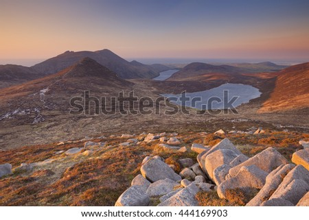 Sunrise over the Mourne Mountains and lakes in Northern Ireland. Photographed from the peak of Slieve Loughshannagh. - stock photo
