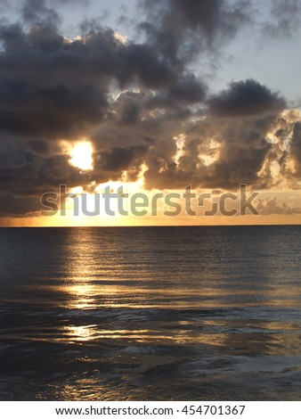 Sunrise over the ocean on a cloudy day - stock photo